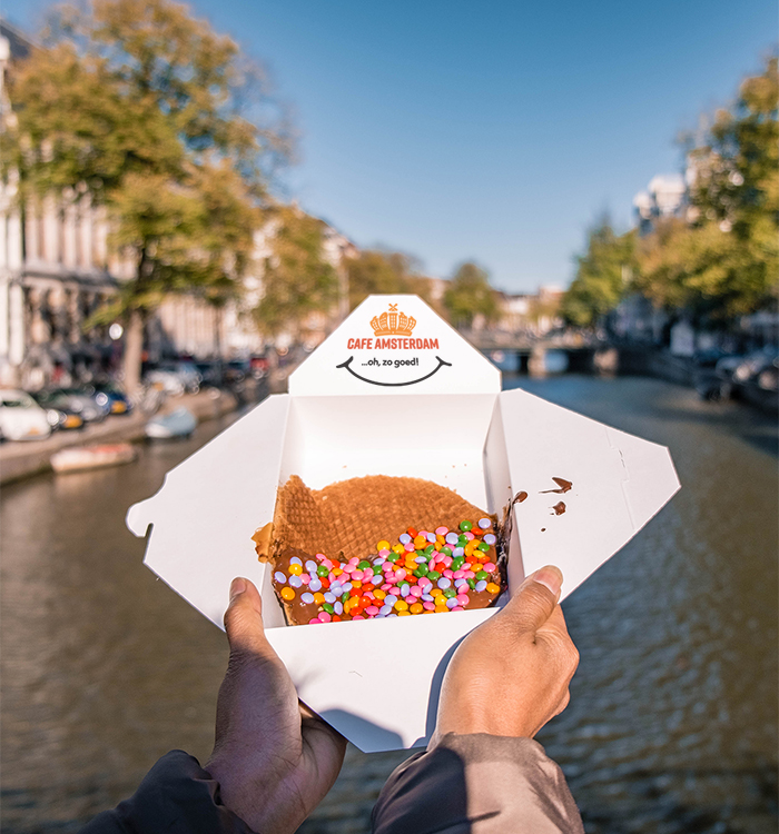 A person enjoys a Cafe Amsterdam Stroopwafel decorated with chocolate and candy