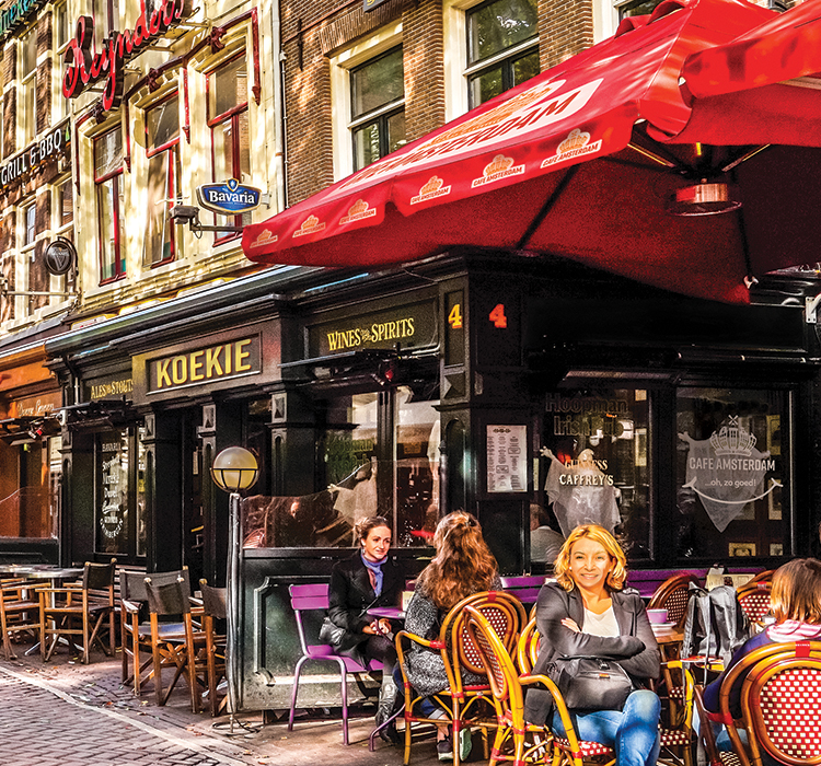 A typical cafe in Amsterdam with Cafe Amsterdam branded patio umbrellas and building signage