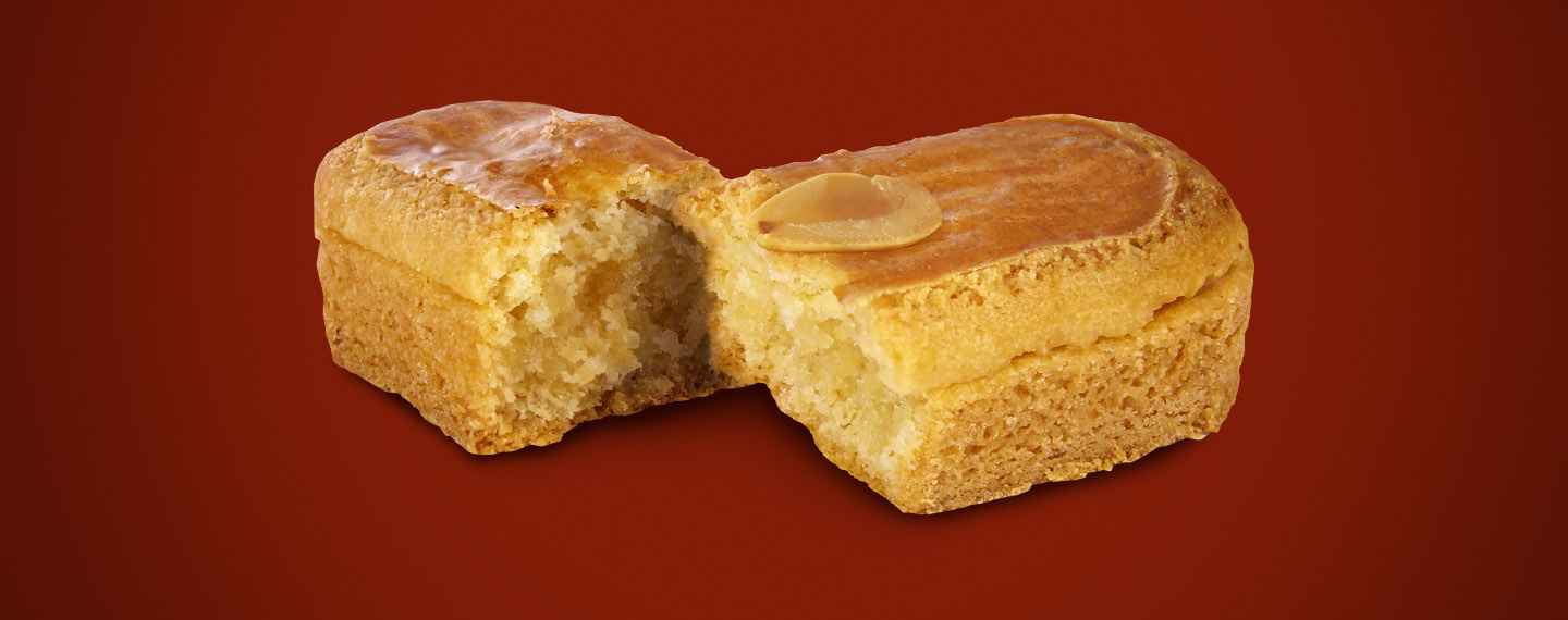 An Almond Finger is broken into two pieces to showcase its almond paste filling.