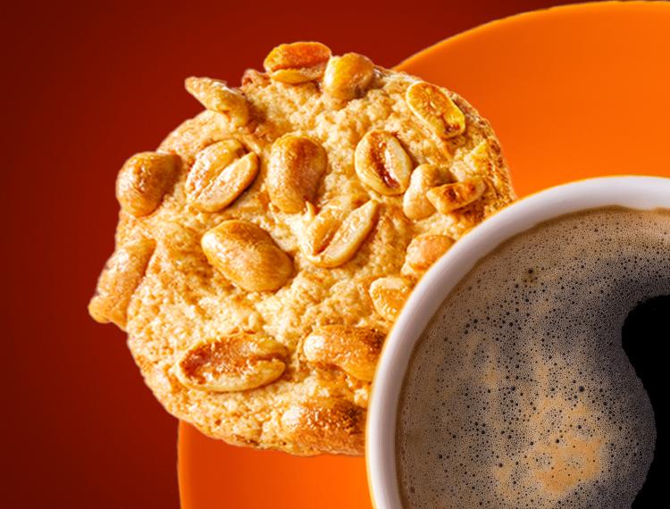 A Peanut Koekie served alongside a cup of coffee